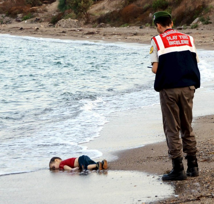 ATTENTION EDITORS - VISUALS COVERAGE OF SCENES OF DEATH OR INJURYA Turkish gendarmerie stands next to a young migrant, who drowned in a failed attempt to sail to the Greek island of Kos, as he lies on the shore in the coastal town of Bodrum, Turkey, September 2, 2015. At least 11 migrants believed to be Syrians drowned as two boats sank after leaving southwest Turkey for the Greek island of Kos, Turkey's Dogan news agency reported on Wednesday. It said a boat carrying 16 Syrian migrants had sunk after leaving the Akyarlar area of the Bodrum peninsula, and seven people had died. Four people were rescued and the coastguard was continuing its search for five people still missing. Separately, a boat carrying six Syrians sank after leaving Akyarlar on the same route. Three children and one woman drowned and two people survived after reaching the shore in life jackets. REUTERS/Yasar Anter/DHA  ATTENTION EDITORS - NO SALES. NO ARCHIVES. FOR EDITORIAL USE ONLY. NOT FOR SALE FOR MARKETING OR ADVERTISING CAMPAIGNS. THIS IMAGE HAS BEEN SUPPLIED BY A THIRD PARTY. IT IS DISTRIBUTED, EXACTLY AS RECEIVED BY REUTERS, AS A SERVICE TO CLIENTS. TURKEY OUT. NO COMMERCIAL OR EDITORIAL SALES IN TURKEY. TEMPLATE OUT